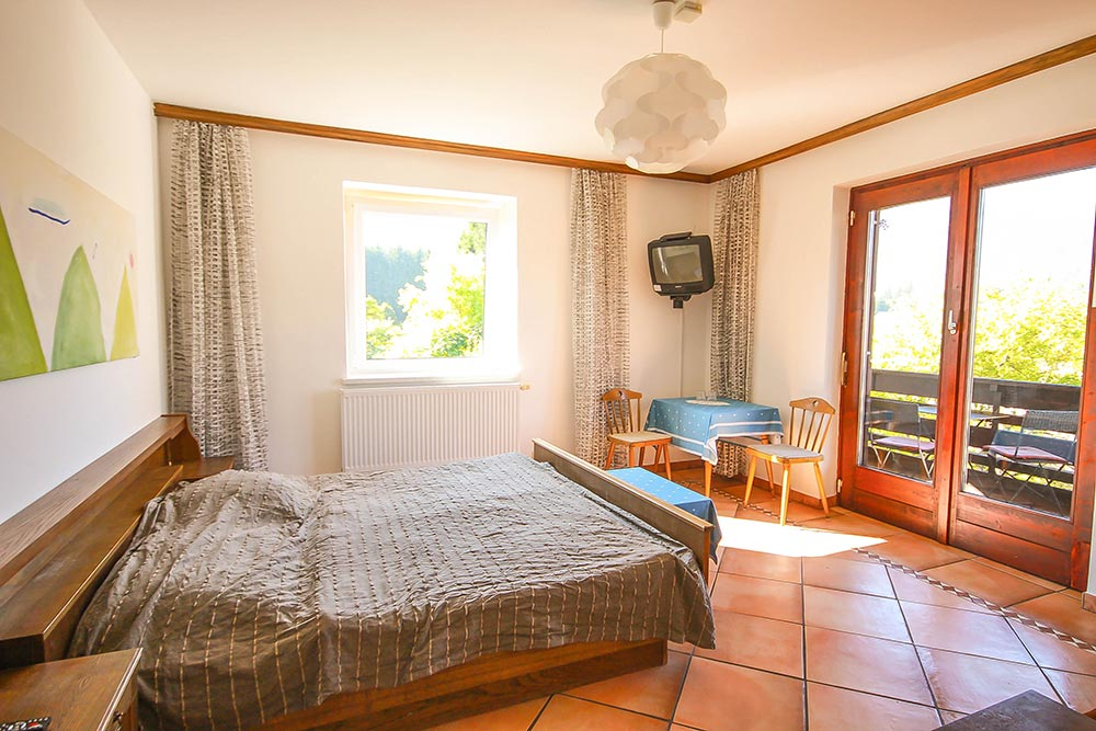 Das Zimmer 2 im Gästehaus Huss - Ansicht auf das Bett, Fenster und Balkon